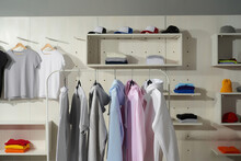 Clothes At Custom Clothing Printing Company. Set Of Blank Pastel Cotton White, Gray, Blue And Pink Sportswear On A Rail In The Store