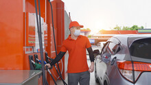A Caucasian Man, People, Worker Filling Up Fuel By Using Petrol Pump At Gasoline Petrol Station, Wearing A Face Mask. Refuel Petroleum Oil And Energy Vehicle Business Service. Coronavirus Pandemic.