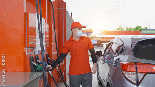Fotografie, Tablou A Caucasian man, people, worker filling up fuel by using petrol pump at gasoline petrol station, wearing a face mask