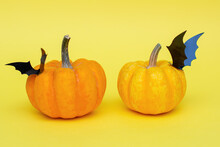 Orange Halloween Pumpkins With Carved Black Decorative Bats On Them, On A Yellow Background.