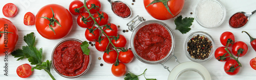 Photo Bowl and jar with tomato paste on white wooden background with ingredients