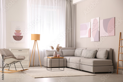 Stylish living room interior with big comfortable sofa and pictures - fototapety na wymiar