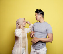 Women Wearing Hijab Happy To Men Smile With Very Happy Expressions Looking At Each Other Isolated On A Yellow Background