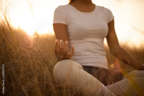 African young woman in nature sitting in yoga position. Focus is on hand. - fototapety na wymiar