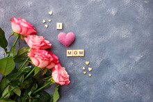 Mothers Day Greeting Card Concept. Bouquet Pink Roses With Letters In Word I Love Mom On Blue Background. Flat Lay Floral Composition