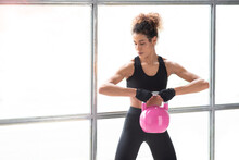Close Up Of Young Beautiful Woman Doing Crossfit Russian Swing In A Gym With A Pink Kettlebell. White Background Horizontal View