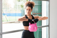 Close Up Of Young Beautiful Woman Doing Crossfit Russian Swing In A Gym With A Pink Kettlebell Horizontal View