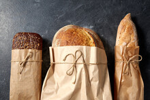 Food, Baking And Cooking Concept - Close Up Of Bread In Paper Bags On Table Over Dark Background