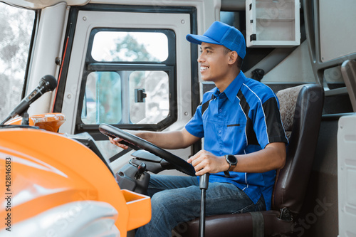 Obraz close up of a male driver in uniform holding the steering wheel and gear lever in the bus - fototapety do salonu
