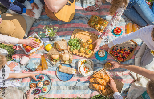 Obraz Picnic setting with burgers, tart, croissant, cakes, picnic hamper basket, guitar and food ready for party. Cheerful family sitting on the grass during a picnic in a park. Young smiling family - fototapety do salonu