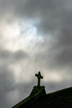 Religious Cross On Ancient Church Building Roof In Cloud With Pale Sun