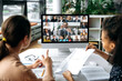 Virtual meeting online, video call. View over shoulders of two women to a computer screen with business leader and successful team, chatting by a video conference, discuss working issues, strategy