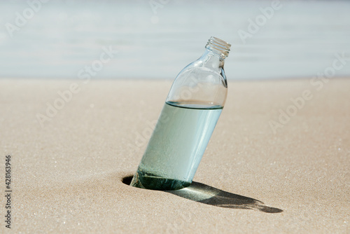 Obraz reusable water bottle on the sand of a beach - fototapety do salonu