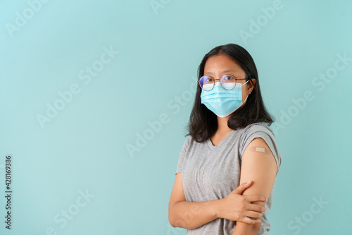 Photo Asian women wearing face mask vaccinated Showing arm bandage to protect COVID-19 spread on blue background