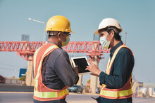 Asian Male Engineer Stands To Discuss At An Elevated Road Construction Site.