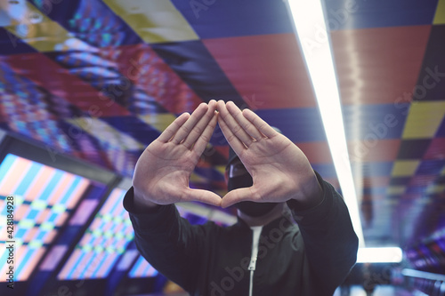 Photo person making triangle hand sign with light flares