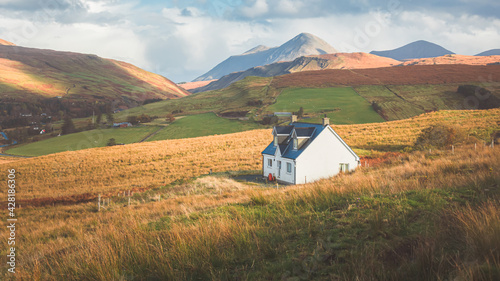 Tela A lone traditional Scottish Highlands white croft house cottage in a rural mountain landscape countryside with Glamaig Peak and the Red Cuillins on the Isle of Skye, Scotland