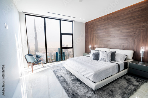Modern and luxurious bedroom with white ceiling and wood accents with views of downtown Dubai skyline Fototapeta