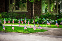 Landscaped House With Big Windows And Many Small American Flags Stuck In Yard Around Drive In Summer.
