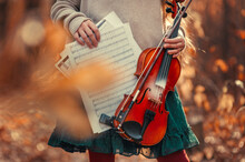 Female Hands Hold A Violin And Sheet Music Among The Autumn Foliage