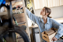 Young Handywoman Searching Some Working Tools On A Wooden Shelves In The Workshop. Concept Of Organization In Home Workshop Or Storage