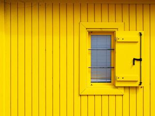 Ventana abierta en una fachada amarilla de una cabaña de madera
