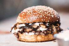 A Delicious Burger With Mushroom Slices Looking Very Dense.