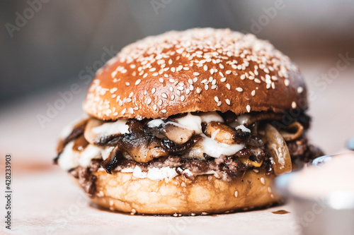 Canvas-taulu A delicious burger with mushroom slices looking very dense.