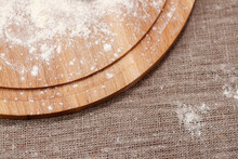 Round Cutting Board In Flour Against The Background Of Burlap