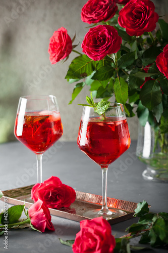 Fotografija Two alcohol cocktails set with red roses