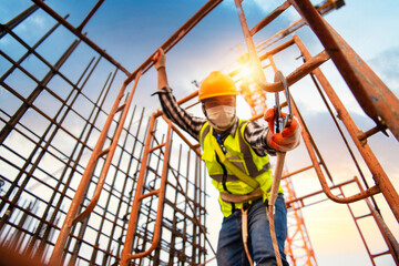 Construction workers wear safety harnesses and harnesses to work at heights during disease (COVID-19).