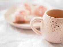 Pink Mug And Little Pink Cakes On A White Bright White Background.