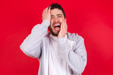 Young Gloomy Young Handsome Caucasian Man In Sports Clothes Against Red Wall, Hiding Face With Hands Pouting And Crying, Standing Upset And Depressed Complaining About Job Problem.