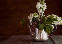 Apple Blossoms, Cherries And Lilacs In An Iron Teapot On A Brown Background