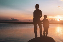 Mom And Her Little Daughter Are Fishing With A Fishing Rod On A Pier At Sunset By The Lake