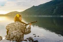 Girl Screaming On The Guitar After Yoga Class, On The Shore Of A Clean Lake, Sitting On The Stones, Against The Backdrop Of Sunset And Beautiful Mountains