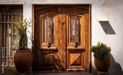Obraz Puerta de madera en casa blanca de estilo mediterráneo en Altea, Alicante. Puerta y fachada vintage.  - fototapety do salonu