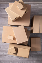 Stack Of Cardboard Box On Floor Laminate Background. Cardboard Boxes For Moving To New Home