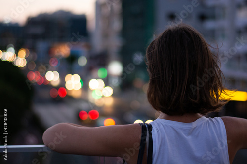 Young woman standing on urban bridge watching city traffic Fototapeta