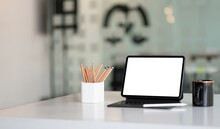 Mock Up Digital Tablet With Blank White Screen On Workplace At Office.
