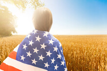 Young Little Girl Holding American Flag On Amazing Sky, Mountain And Meadow Nature Background At Sunset.