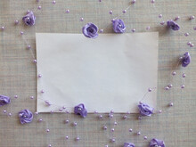 White Sheet Of Paper On A Gray Fabric Background, Decorated With Purple Artificial Roses And Beads