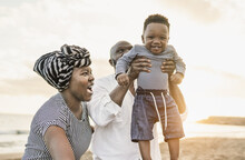Cute African Toddler Smiling In Camera - Black Family Enjoy Summer Vacation On The Beach - Mother, Father And Child Love