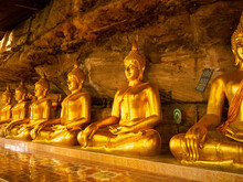 The Golden Statues In The Cave At Tham Khuha Sawan Temple. Ubon Ratchathani, Thailand.