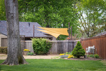 Yard Of Fun House In Early Spring With Shade Sails And Privacy Fence And Harge Trees - Landscaping And Outside Seating.