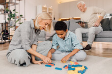 Woman And Her Multiracial Son Sitting At The Carpet And Putting Jenga