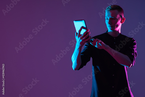 Obraz Portrait of a man with a tablet. Student looks at screen of the tablet. Guy is holding gadget in front of him. Student with a tablet on a purple background. Concept - sale of tablets for study. - fototapety do salonu