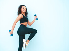 Fitness Smiling Black Woman In Sports Clothing With Afro Curls Hairstyle.She Running And Jogging . Young Beautiful Model With Perfect Tanned Body.Female Holding Dumbbells In Studio Near Blue Wall
