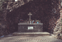 Tomb With A Big Wooden Cross And Religious Souvenirs Under The Rocky Cave