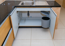Closeup Of The Opened Kitchen Sink Cabinet With A Plastic Trashcan